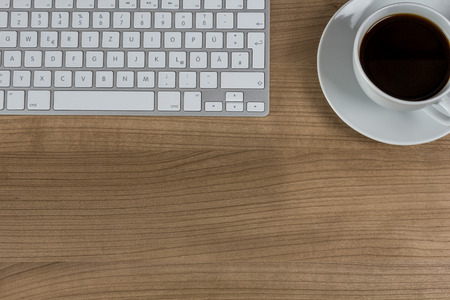 lifestile: Modern keyboard and a cup of coffee on a wooden Desktop