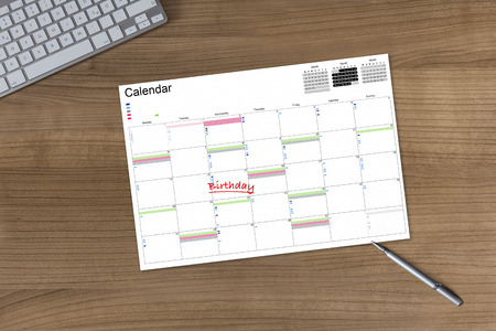 Calendar with the word Birthday on a wooden table with modern keyboard and silver pen photo
