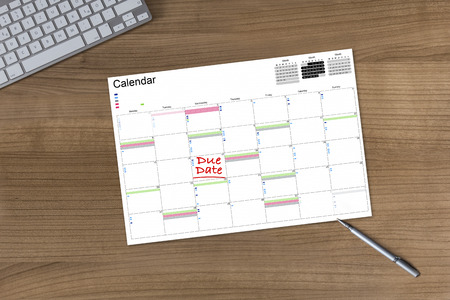 due date: Calendar with the words Die Date on a wooden table with modern keyboard and silver pen