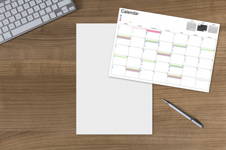 Calendar and a blank sheet on a wooden table with modern keyboard and silver pen Stock Photo
