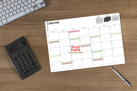 due date: Calendar with the words Due Date on a wooden table with calculator modern keyboard and silver pen
