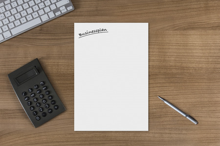 businessplan: Blank sheet with the headline Businessplan on a wooden table with modern keyboard calculator and silver pen Stock Photo