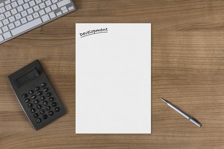 Feuille blanche avec le titre du d�veloppement sur une table en bois avec la calculatrice clavier moderne et un stylo en argent