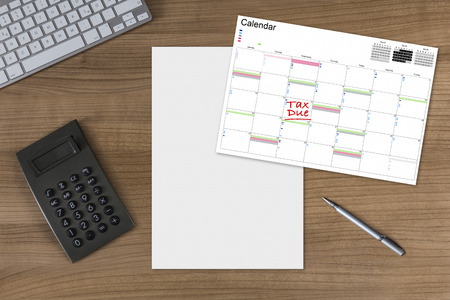 Calendar with the words Tax Due and white sheet on a wooden table with calculator modern keyboard and silver pen