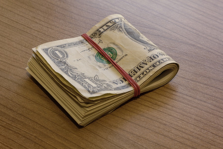 showoff: Bundle of dollar notes on a wooden table