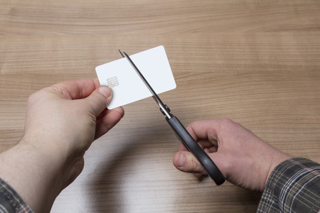 smashup: Two hands holding and cutting a blank white credit or debit card
