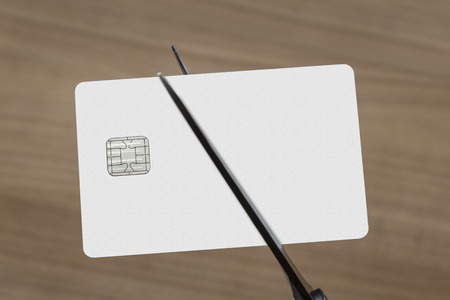 smashup: scissors cutting a blank white credit or debit card