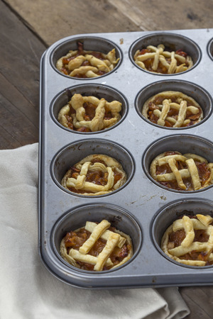 Mini apple pies in a muffin tray photo