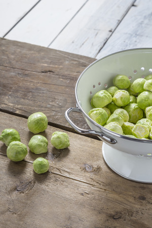 Brussels sprouts in a sieve on a wooden table Stock Photo