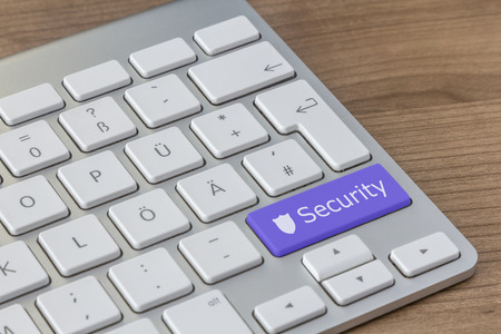 computer attack: Security and shield icon on a large blue button of a modern keyboard on a wooden desktop
