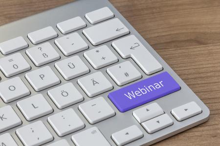 Webinar written on a large blue button of a modern keyboard on a wooden desktop