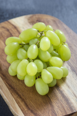 fresh green grapes on wooden board