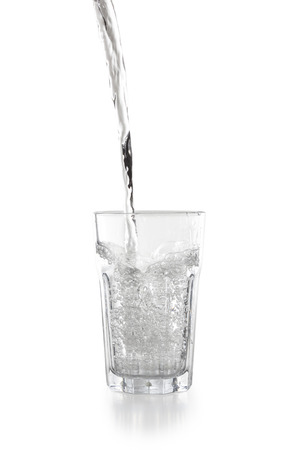 Water pouring into a glass isolated on white background Stock Photo