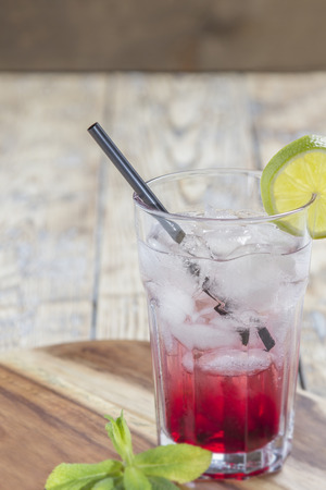Glass with Red Drink on ice with lime slice and mint leaves on rustic wooden background