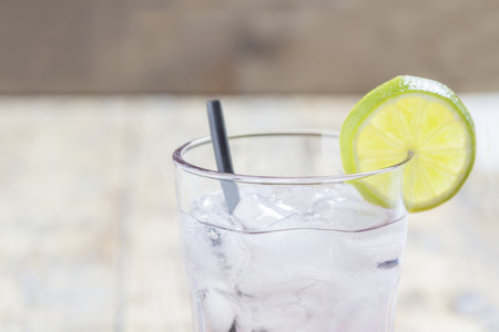 fruit in water: A glass filled with a transparent liquid, ice cubes and a lime slice with a straw on wooden table