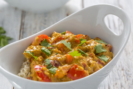 curry bowl: chicken curry, red pepper and coriander leaves with rice in a white bowl Stock Photo