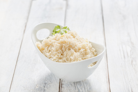 bowl with rice: Boiled Rice in a bowl on a white table
