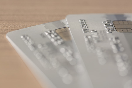 cloesup: Cloesup view of two silver credit cards on a wooden table