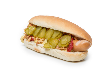 Hot Dog sausage in a bun with roasted onions, pickles, ketchup and mustard on white background Stock Photo