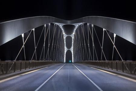 costruction: Road on modern frame bridge illuminated at night Stock Photo