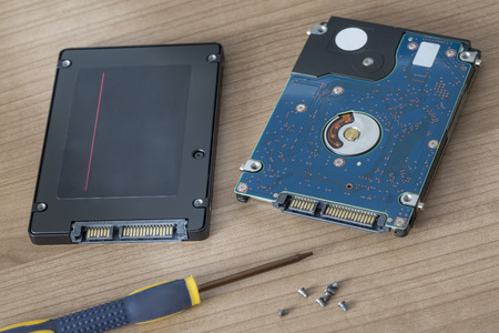 solid state drive: Physical Hard Disr drive being replaced by a solid state flash drive Stock Photo