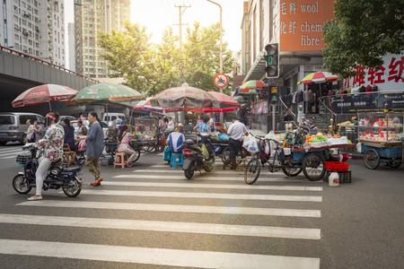 streetlife: SHANGHAI - JUNE 11: Food being sold on an crosswalk in front of the South Bund soft spinning material market. June 11, 2015 in Shanghai