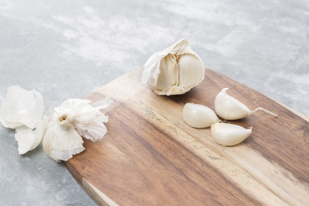 skinning: Garlic bulb and single cloves on a wooden board