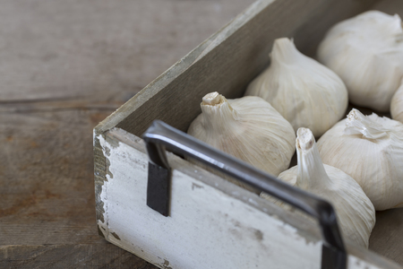 skinning: Garlic bulbs in a rustic wooden box on a wooden table