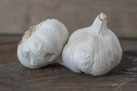 skinning: Two Garlic bulbs on rustic wooden background