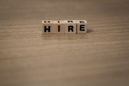 employe: Hire written in wooden cubes on a desk Stock Photo