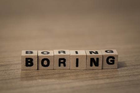 Boring written in wooden cubes on a desk Stock Photo