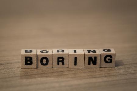 ennui: Boring written in wooden cubes on a desk Stock Photo