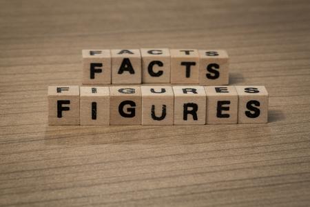 机の上に木製のキューブで書かれて事実と数字