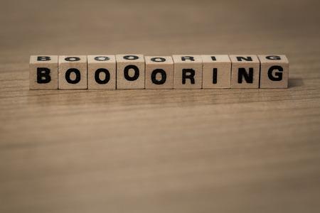 Booooring written in wooden cubes on a desk