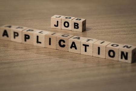 employe: Job Application written in wooden cubes on a desk Stock Photo