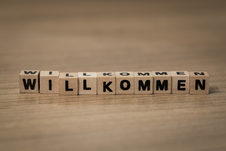 willkommen: Willkommen (German welcome) written in wooden cubes on a desk Stock Photo