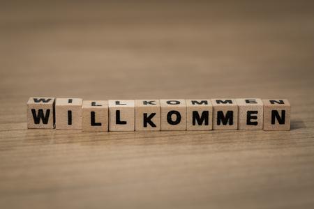willkommen: Willkommen (German welcome) written in wooden cubes on a desk Stock Photo