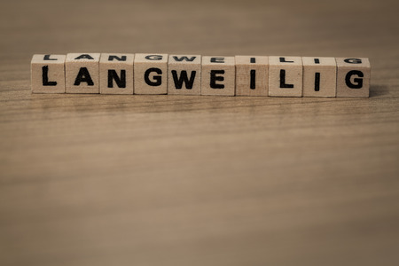 Langweilig written in wooden cubes on a desk Stock Photo