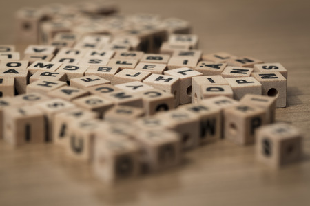messily: small wooden cubes messily on a desk