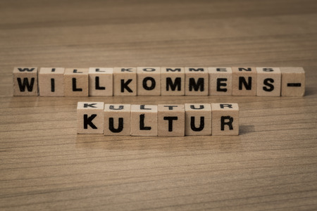 german culture: New german word creation Willkommenskultur (welcoming culture) used when  migrants are integrated in existing communities, written in wooden cubes on a desk