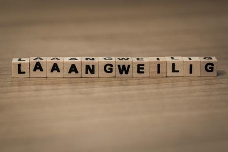 ennui: Laaaangweilig (German Booooring) written in wooden cubes on a desk