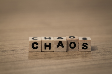 chaos: Chaos written in wooden cubes on a desk Stock Photo