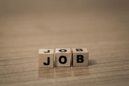 employe: Job written in wooden cubes on a desk