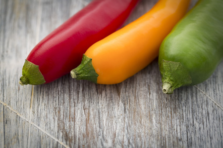 health symbols metaphors: Closeup of red yellow and green Chilli on rustic wooden table Stock Photo