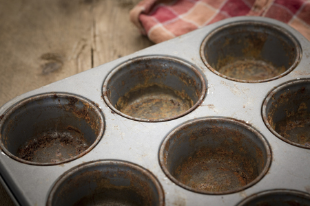 rustiness: Dirty rustic rusty muffin tray on wooden background