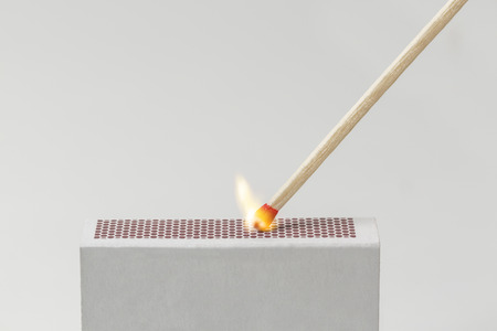 A Match being lit with the striking surface of a matchbox Stockfoto