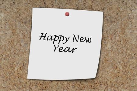 memo board: Happy new year written on a memo pinned on cork board