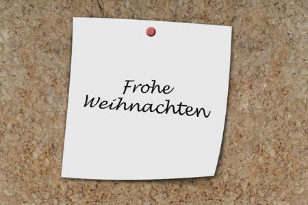 weihnachten: frohe weihnachten (German Merry christmas) written on a memo pinned on a cork board Stock Photo