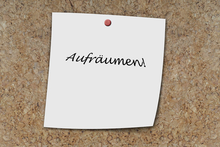 clean up: Aufr�umen (german clean up) written on a memo pinned on a cork board