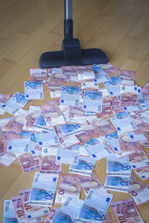 household money: A Vacuum cleaner soaking in euro notes on a wooden floor